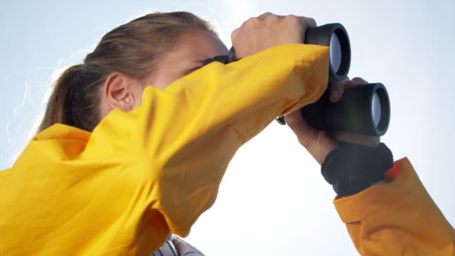 woman with binoculars - looking through an object stock videos and b-roll footage