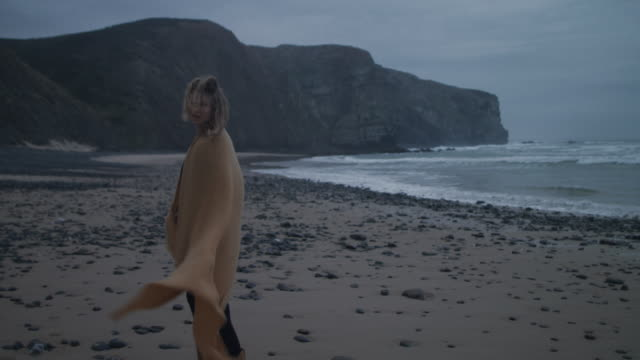 Woman with blanket walking on deserted beach