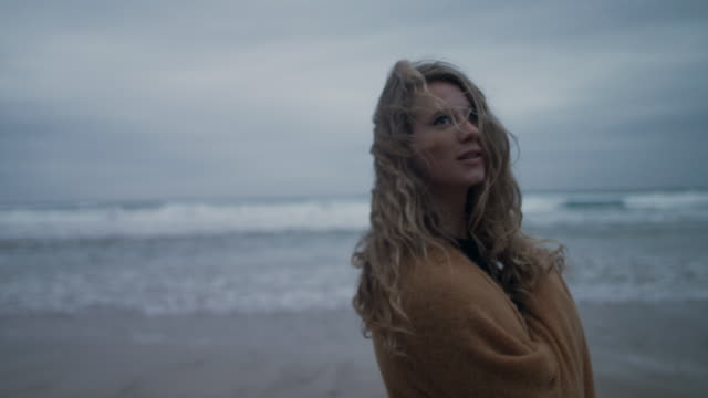 woman with blanket walking on deserted beach - capelli biondi video stock e b–roll
