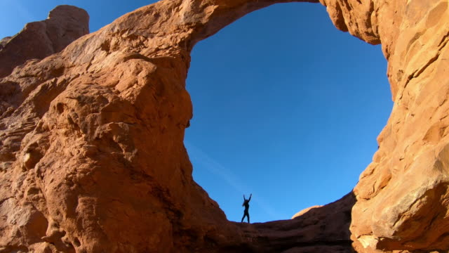 woman with blond hair doing gymnastics, Arches National Park