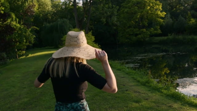 vidéos et rushes de woman with blond hair wearing straw hat turning around, laughing and hiding from camera, summertime feeling in green garden, slow motion - chapeau de paille