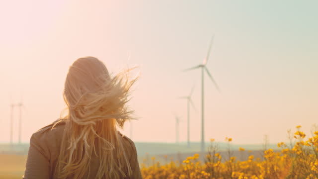 vídeos de stock e filmes b-roll de super slo mo - time warp effect woman with blond long hair running along wind turbines - emotion