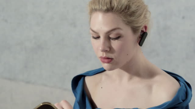 vidéos et rushes de woman with bluetooth device in ear applies concealer - châle