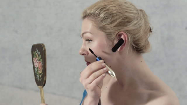 woman with bluetooth device in ear looks into mirror and applies mascara.  - pampering self stock videos and b-roll footage