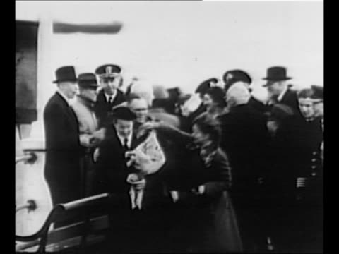 woman with bouquet stands with crowd at harbor in falmouth, england; she is the mother of ss flying enterprise captain henrik kurt carlsen, who... - basco video stock e b–roll
