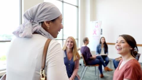 vídeos y material grabado en eventos de stock de mujer con cáncer de mama es recibida por amigos antes de la reunión del grupo de apoyo al cáncer de mama - comunidad