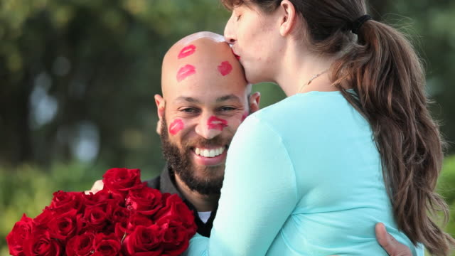 cu woman with bright red lipstick kissing bald man's head / richmond, virginia, usa - verlieben stock-videos und b-roll-filmmaterial