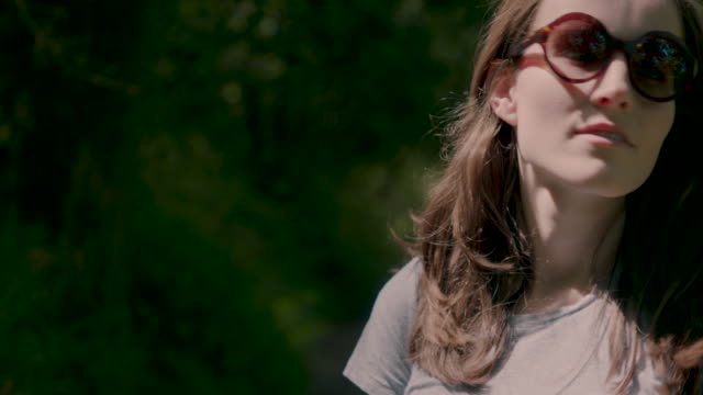 woman with brown hair and sunglasses in forest - kopf nach hinten stock-videos und b-roll-filmmaterial