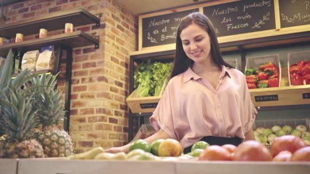 vídeos de stock, filmes e b-roll de mulher com as frutas de compra do cabelo marrom em um verdureiro que sorri muito - feirante