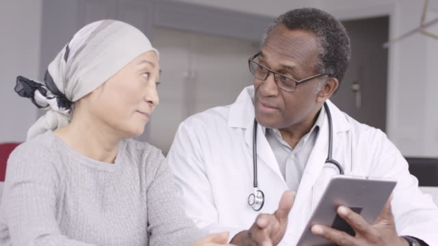 Woman with cancer reviews test results with doctor