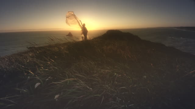 MS SLO MO POV Woman with cape in wind by Ocean at sunset / Cape Blanco, Oregon, United States