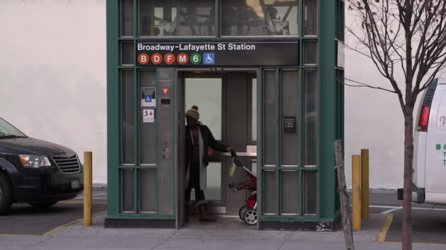 Woman with Carriage Using Subway Elevator