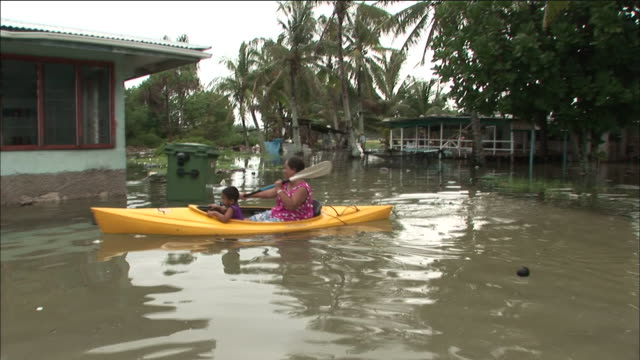 stockvideo's en b-roll-footage met woman with child rows kayak through flooded village funafuti tuvalu - pacifische eilanden