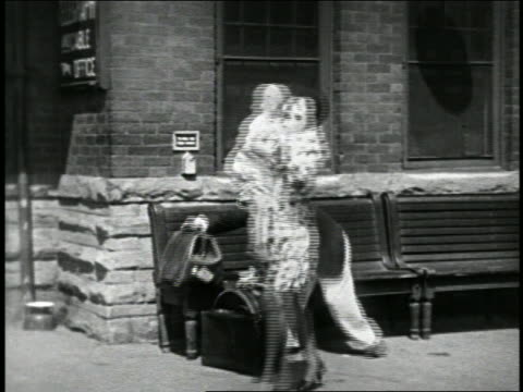 stockvideo's en b-roll-footage met b/w 1925 woman with child sneezing + leaving train depot bench / sneezing man follows with luggage - 1925