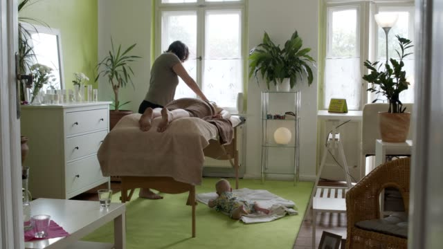 stockvideo's en b-roll-footage met woman with child works from home and offers massages to other mothers - massagetafel