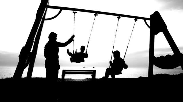 vídeos de stock e filmes b-roll de mulher com criança em um balanço da costa - baloiço