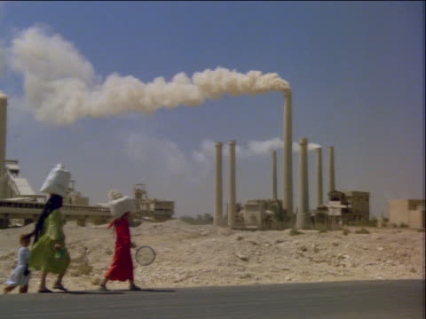 Woman with children walking with bags on head / smokestacks background