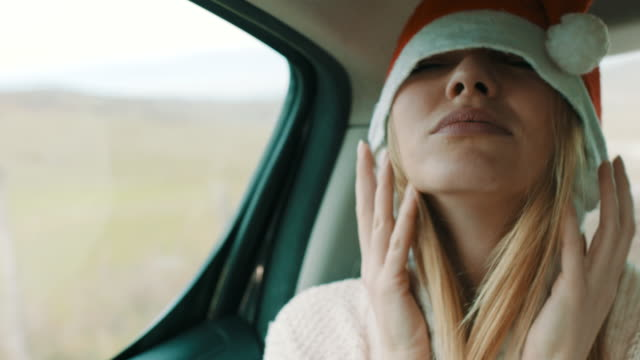 woman with christmas hat on her head having fun on back seat of the car - young women stock videos & royalty-free footage