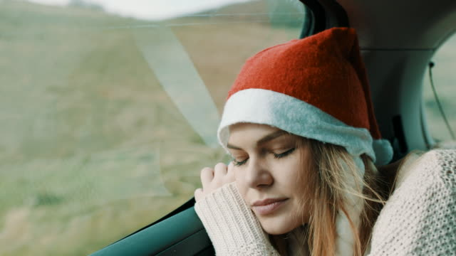 vídeos de stock e filmes b-roll de woman with christmas hat on her head sleeping on back seat of the car - chapéu