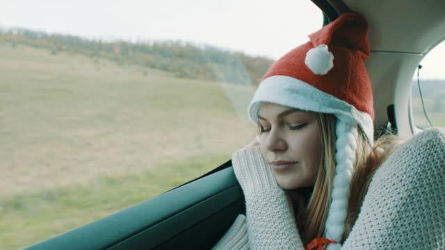 車の後部座席で寝ている彼女の頭の上のクリスマス帽子の女