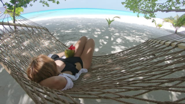 MS Woman with coconut drink in hammock on tropical ocean beach,Maldives