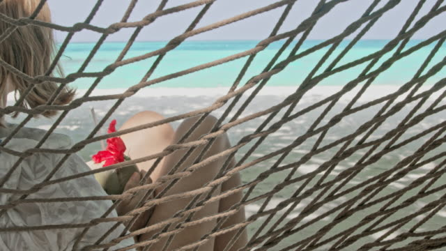 cu woman with coconut drink relaxing in hammock on tropical ocean beach,maldives - tropical drink stock videos and b-roll footage