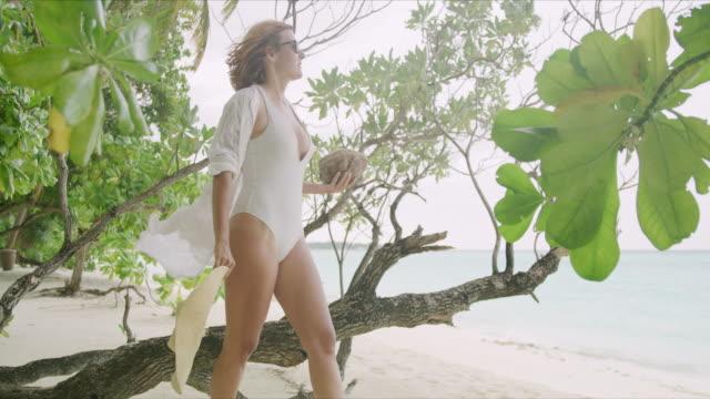 MS-Woman mit Kokosnuss zu Fuß am Strand tropischen Meer, Malediven