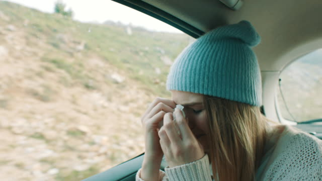 Woman with common cold sitting on back seat of the car