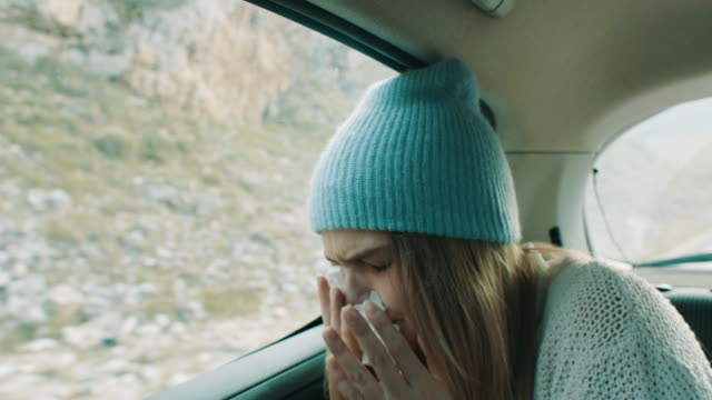 woman with common cold sitting on back seat of the car - allergy stock videos & royalty-free footage