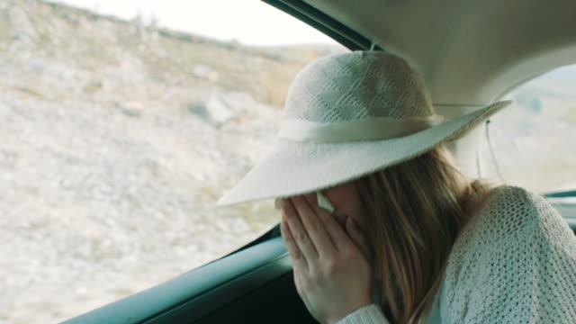 vídeos y material grabado en eventos de stock de mujer con resfriado común sentado en el asiento trasero del coche - estornudar
