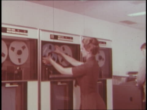 stockvideo's en b-roll-footage met 1961 rear view pan woman with computer reels + men with printouts - 1961