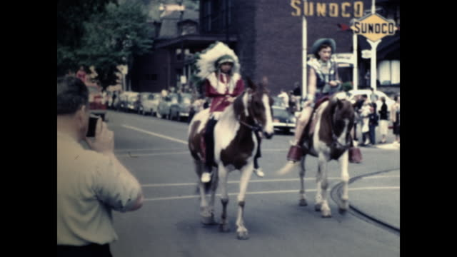 woman with cowboy hat on horseback holding american flag leading cars; red cart pulled by horses; person in native american outfit on horseback; sign... - the cars stock videos & royalty-free footage
