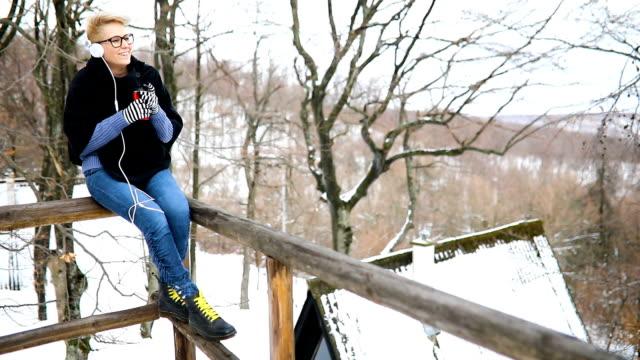 vidéos et rushes de femme avec une tasse de boisson chaude, écoutant de la musique sur son casque à la journée d'hiver enneigée - manteau et blouson d'hiver