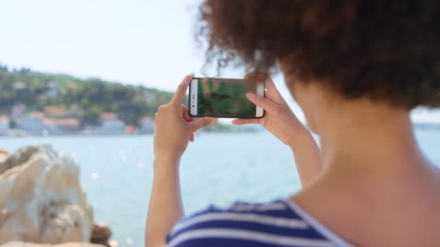 Woman with curly hair talking a photo of the town by the sea with her smartphone on a sunny day
