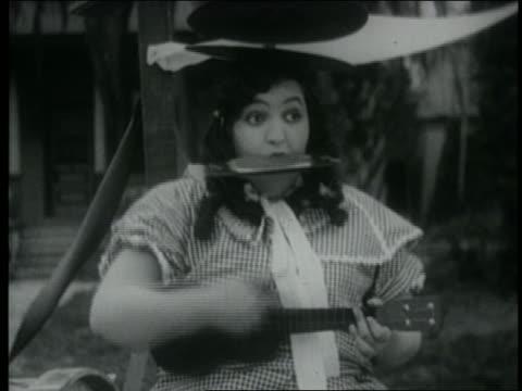 B/W 1920 woman with cymbal on head playing harmonica + ukelele
