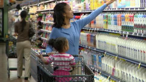 ms woman with daughter (2-3) sitting in shopping trolley choosing yoghurt in supermarket, richmond,  virginia, usa - stormarknad bildbanksvideor och videomaterial från bakom kulisserna