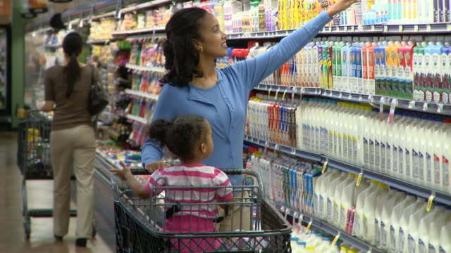 ms woman with daughter (2-3) sitting in shopping trolley choosing yoghurt in supermarket, richmond,  virginia, usa - スーパーマーケット点の映像素材/bロール