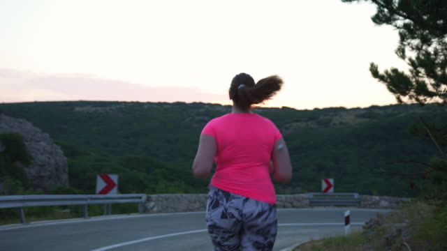 woman with diabetes wearing a cgm and running outdoors in nature - type 1 diabetes stock videos & royalty-free footage