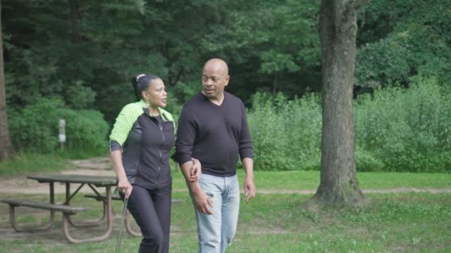 stockvideo's en b-roll-footage met vrouw met verschillende capaciteiten en man geniet van de natuur samen - kruk orthopedische apparatuur