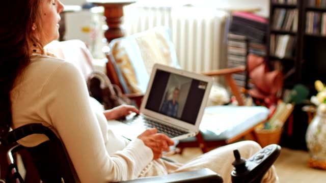 Femme handicapée ayant un chat vidéo avec un ami