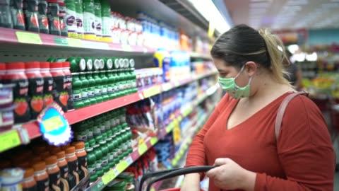 frau mit einweg-medizinmaske einkaufen im supermarkt - merchandise stock-videos und b-roll-filmmaterial