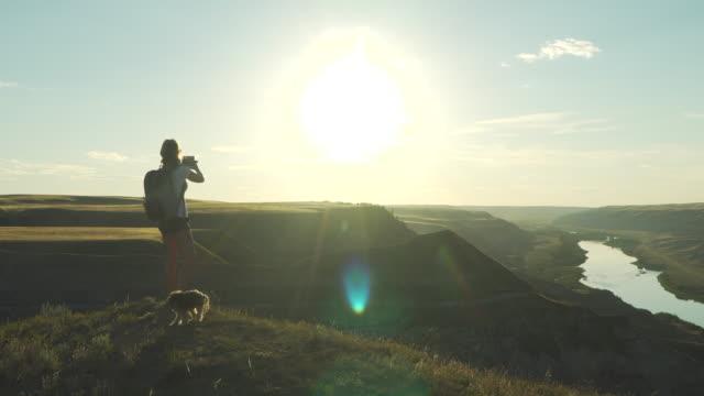 stockvideo's en b-roll-footage met vrouw met hond op de bergtop maakt foto van de zonsondergang - alleen één mid volwassen vrouw