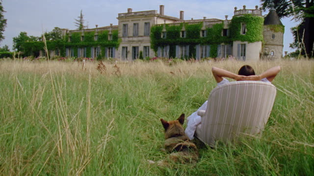 WS, Woman with dog sitting in armchair in front of palace, rear view, Saint Ferme, Gironde, France