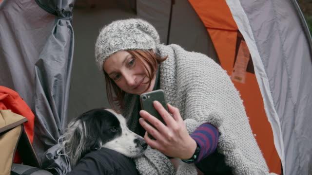 vidéos et rushes de woman with dog taking selfie - photophone