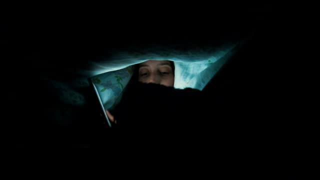 Woman with dog under blanket