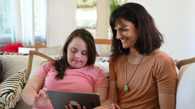 woman with down syndrome using digital tablet with friend - next to stock videos & royalty-free footage
