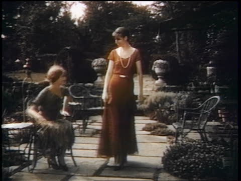 1938 woman with dress standing + walking through garden alongside woman wearing red dress - red dress stock videos & royalty-free footage