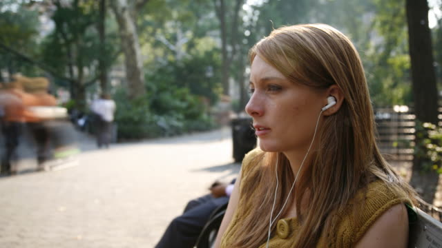woman with earphones on a bench - park bench stock videos & royalty-free footage