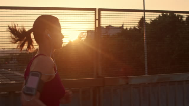slo mo ts woman with earphones running at sunset - back lit stock videos & royalty-free footage