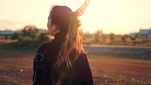 Woman with earphones running in the sunset Time(slow motion)